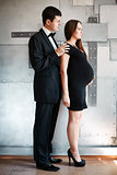 Man and expectant mother standing together.