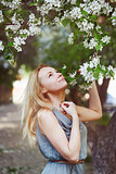 Beautiful young woman is enjoying by spring flowers