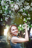 Happy beautiful girl in the park in flowers
