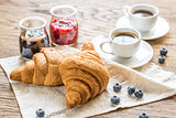 Croissants with fresh blueberry and two cups of coffee