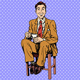 Man drinking tea sitting on the stool