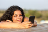 Relaxed girl watching social media in smart phone
