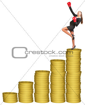 Businesslady in boxing gloves on gold coins stack