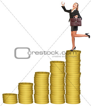 Businesslady with suitcase on gold coins stack
