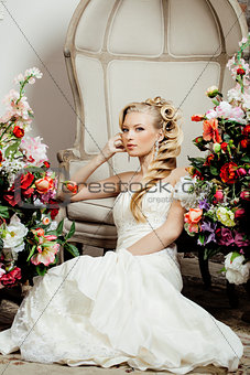beauty young bride alone in luxury vintage interior with lot of flowers