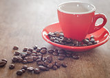 Red coffee cup with coffee beans on wooden table