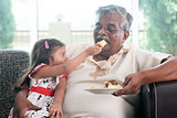 Granddaughter feeding grandfather cake