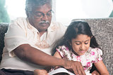 Granddaughter and grandfather reading book