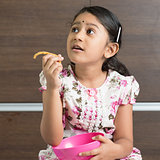 Indian girl eating cookie