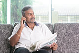 Indian man reading newspaper and calling phone