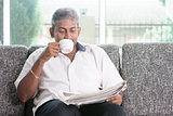 Indian drinking coffee and reading newspaper