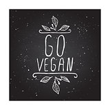 Go vegan - product label on chalkboard.