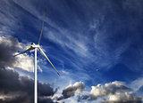 Wind turbine and blue sky with storm clouds
