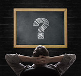 Man looking at question mark on blackboard