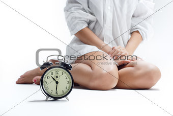 Beautiful female legs and an alarm clock