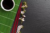 Japanese sushi chopsticks, soy sauce bowl and sakura blossom