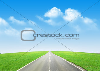 Asphalt road through the green field and blue sky