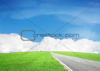 Asphalt road through the green field and sky with clouds