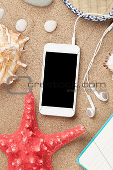 Smartphone on sea sand with starfish and shells