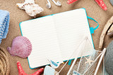 Travel and vacation notepad with items over sand
