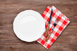 Empty plate and silverware over wooden table