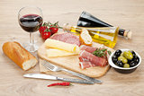 Red wine with cheese, olives, tomatoes, prosciutto, bread and sp