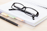 Office table with glasses over notepad