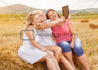 Group of friends in a field taking a picture with a tablet