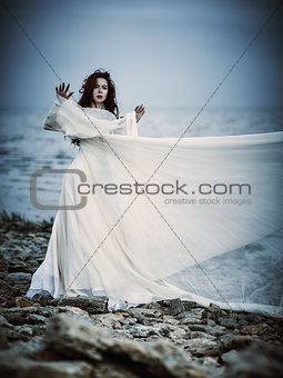 Beautiful sad young woman in white dress standing on sea coast