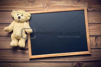 blank chalkboard and teddy bear