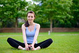 Beautiful Smiling Woman Doing Stretching Exercise on the Grass in the Park