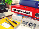 Healthcare on Red Office Folder. Toned Image.