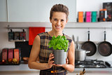 Smiling woman in kitchen holding pot of fresh basil