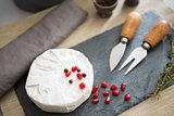 Fresh Camembert cheese on a slate with pomegranate seeds
