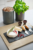 Camembert cheese with fresh herbs, pomegranate, and peppercorns