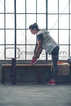 Fit young woman tying shoe on bench by window in city loft gym
