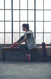 Fit woman sitting in profile in city loft gym tying shoe