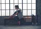 Sporty woman in profile sitting on bench tying shoe in loft gym