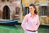 Smiling woman tourist in Venice standing near canal