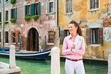 Happy woman tourist in Venice holding map near canal