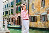 Laughing woman tourist in Venice holding camera near canal
