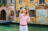Woman tourist in Venice taking selfie and giving thumbs up