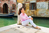 Happy woman sitting and relaxing on pier in Venice