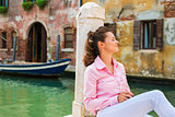 Woman sitting and relaxing on pier in Venice with eyes closed