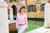 Smiling woman tourist walking along canal in Venice