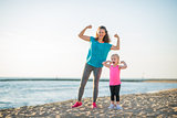 Happy mother and daughter in fitness gear on beach flexing arms