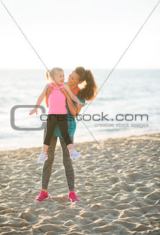 Fit young mother lifting young daughter up on beach at sunset