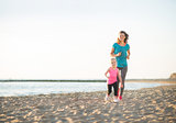 Happy mother and daughter running on beach at sunset