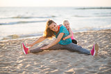 Happy mother exercising with daughter on the beach at sunset
