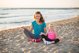Happy mother and daughter sitting in lotus position on beach